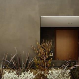 1階 エントランス/外壁の黒色は、光の当たり方でいろいろな顔を見せる。夏には植栽の緑とのコントラストが美しい