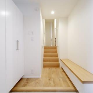 親世帯玄関 /まっすぐなアプローチの先の階段を上りリビングへ。玄関には、高齢の家族のことを考え、座りながら靴が履けるベンチ型収納を設置