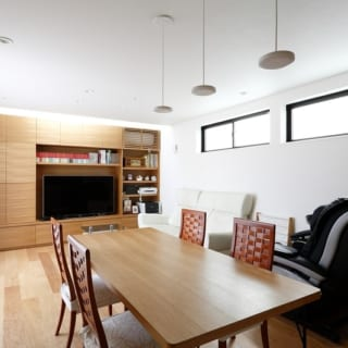 1階 親世帯LDK/テーブルや壁面収納は、西村さんがこの家のためにデザインしたもの。同じオーク材を使うことで温かみのある雰囲気を出している。エアコンも壁面収納に収めることでスッキリとした印象に。壁面収納の上には、トップライトからの光が差し込む