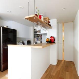 1階 親世帯キッチン/キッチンに設けられたバーカウンター。吊り下げ式のグラスホルダーがちょうどよい高さに設置されている。奥には収納力抜群のパントリースペースがありキッチンをすっきりとさせることができる
