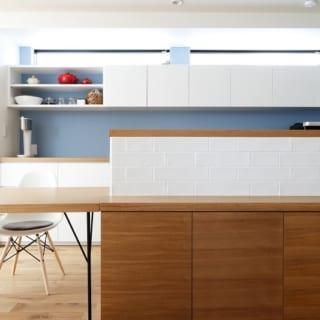 2階 キッチン/キッチンカウンターからフラットに続くダイニングテーブル。高さが揃っているので、まるで一体化しているかのよう。 壁面収納上部に設置した高窓からの光が、キッチンを明るくしている