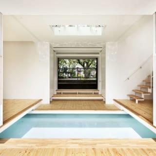 1階玄関ホール北向き/緑豊かな公園に面した玄関を入ると、約2000リットルの雨水を溜める美しい水盤が。写真左手には寝室、右手には桜本さんの事務所兼書斎 があり、写真右の階段は1.5階のキッチンに続く