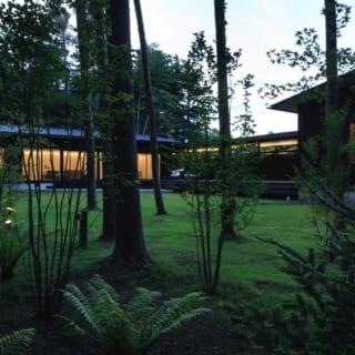 外観 庭/もとは林だった敷地のため、庭はゆるやかに針葉樹の林につながっていく。高原の自然の中にともるK邸のやわらかな光が、心落ち着く穏やかな余暇を物語る