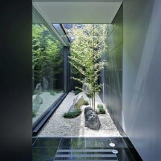 【写真】玄関ドアを開けると目の前にある和の庭。上に向かってスッと伸びるクロチクと、採石場まで行って選んできたという石が風格を漂わせる
