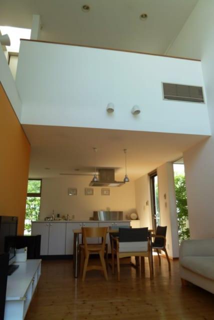 白と木を基調としたモダンなLDKは、すっきりと美しい空間を保てるよう、あらかじめ収納スペースを造作。窓の外のグリーンと一面だけオレンジに塗った壁が彩りを添える