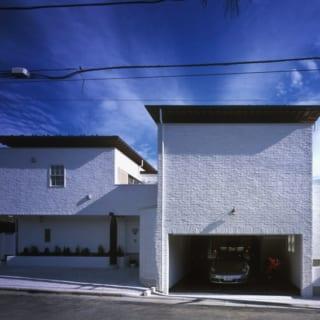 """外観 表/敷地の傾斜を活かし、リビングを""""半地下""""としたM邸。清潔感があり温かみも感じられる白いレンガタイルの外壁は、奥さまの希望で選んだもの"""