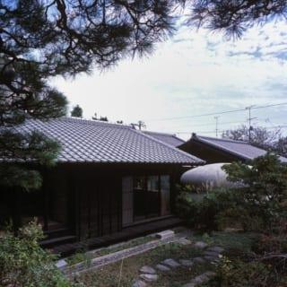 外観/立派な松が印象的な庭に向け、大きく開いた窓を設置。居住空間のどこからも美しい眺めを楽しめる。外壁は、木目の風合いを引き立てるオイル塗料で仕上げた黒いスギ板張り。規則正しく並んだ瓦屋根が重厚感を醸し、凛とした佇まいに