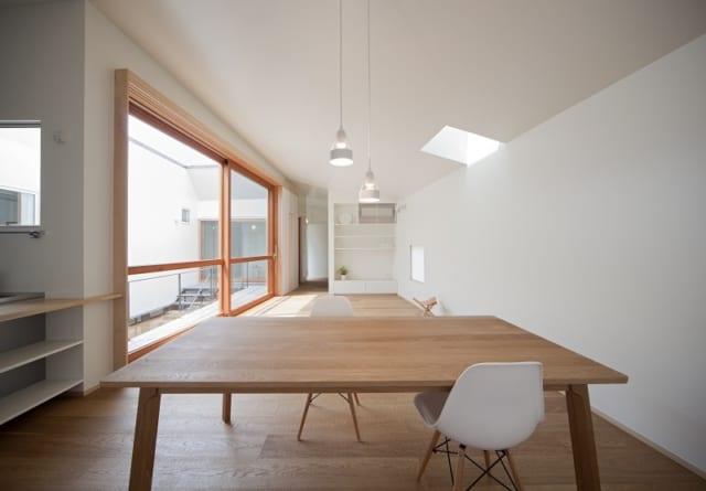 中庭に面した大きな窓や天窓から光をいっぱいにとりいれたLDK。室内も中庭の壁もまっ白で、より明るく感じさせる
