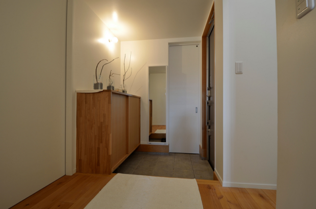 1階 玄関/落ち着いた木の風合いで温かみを感じる玄関。写真奥の白い扉はコートなどを収められる収納スペースとなっている
