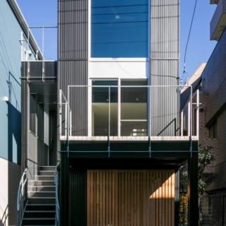 黒・シルバー・白を基調とした建物に、ガレージの扉に使用された木製の格子戸が温かみを加える