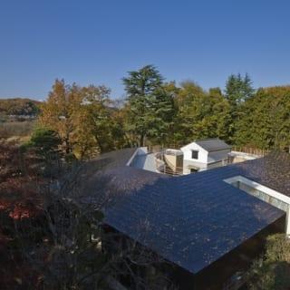 """外観全体 上から/家屋を囲む豊かな森もK家の敷地。家屋は蔵の建つ中庭をぐるりと囲むように建つ。中庭を挟んで向き合う2つの世帯を大きな屋根が覆ってつなぎ、""""ひとつ屋根の下""""での暮らしを表現する"""