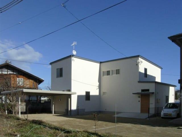 青い空に映える白い外観。壁は白いジョリパット吹付け、屋根にはガルバニウム鋼板を使用した