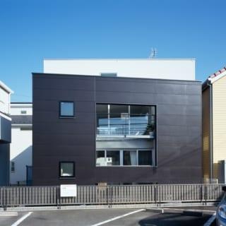 白い建物をぐるりと囲むように設けた黒い壁。白い壁と黒い壁の開口部の位置をずらし、採光とプライバシーを両立した。黒い壁の高さ、開口部の位置は、子世帯、親世帯それぞれの身長から細かくシミュレーションして決めている。