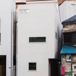 外観/大通りから見たK邸。白いすっきりとした外観だが正面から見るとほとんど窓がなく、一見すると邸内の想像がつかない。建物の脇には細長いアプローチがあり、手前に店舗への出入口、奥に自宅玄関がある。工法は鉄筋コンクリート造などで用いられるラーメン構造を木造にとり入れたもので、耐震性が高い