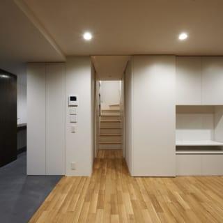 1階 居室/1階の居室より、奥側の階段を臨む。左側が現在ご主人の仕事場で、床暖房も入っており暖かい。将来キッチンにした場合のことも考え床の素材はモルタルに