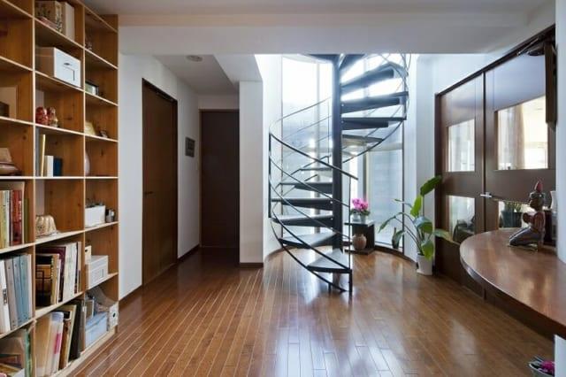 7階(自邸)玄関ホール/邸内に入ると、ゆったりとした玄関ホールと美しい曲線を描く螺旋階段がお出迎え。半円形のガラス越しには光をとり込む中庭もある。写真右の南側がLDKへの入口、写真奥が和室、写真左の北側は応接間と水まわり