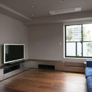 リビング/内装の床や壁の素材に合わせて、ブラックウォルナットと、ビーズブラスト加工を施したステンレスでテレビボードを設えた。上品な質感が高級感を醸すと共に、やわらかな反射光で空間の広がりを演出する