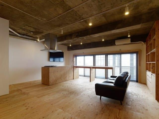 ワンルーム/床と家具に構造材であるラーチ合板を用いてコストダウンを図ったワンルーム空間。壁にはボードに塗装を施したものを使用した
