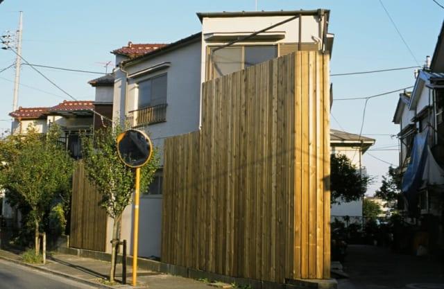 木造の柵で覆われた外観はモダンな印象。玄関替わりの扉を開けると、バリアフリーでそのまま部屋に入れる