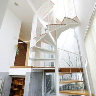 """螺旋階段・中庭/1階から2階への螺旋階段に沿った北東角に、邸内の""""タテの空間""""をつなぐ吹抜けの中庭をしつらえた。『タテノニワ』と名づけたこのスペースのおかげで、家の中の広い範囲に自然光の明るさがおよぶ"""