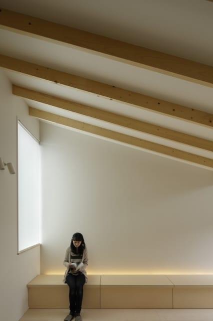 繁田諭   【写真2】C棟 2階 リビングダイニング/腰掛にも使えるゆったりとした備え付けの収納ベンチ。写真のダイニング側は上蓋が開き、リビング側はTV台としての利用も想定し引き出しタイプに
