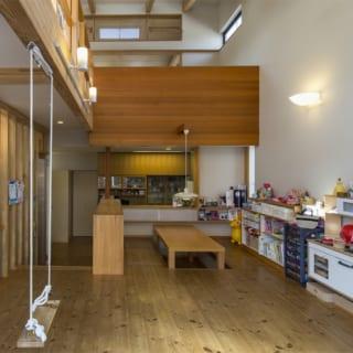 2階 リビング~ダイニング~キッチン、3階への階段/キッチンカウンターの目の前にあるダイニングテーブルは堀座卓。一段低いキッチンに立つ人と目線が同じ高さになる。空間的にもテーブル&椅子よりすっきりした印象に。3階ロフトの大梁下にはブランコを設置し、お子さんお気に入りの遊び場になっている