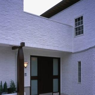 外観 玄関/柔らかな曲線を描くアプローチは石敷き。外壁の真っ白なレンガタイルと色味や質感の相性が良く、洗練されたヨーロッパの邸宅を彷彿とさせる