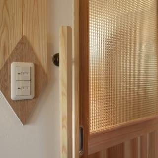 1階 玄関からLDKへの引き戸/玄関を入ると左手にLDKへの引き戸がある。最近は建具にアクリル板を用いるケースが多いが、福田さんはガラスを使う。「やはり質感や光の反射がきれいです」。スイッチプレートはひし形の飾り板に設置。邸内のところどころにひし形のモチーフがあり、整然としたデザインの中のちょっとした変化が目に楽しい