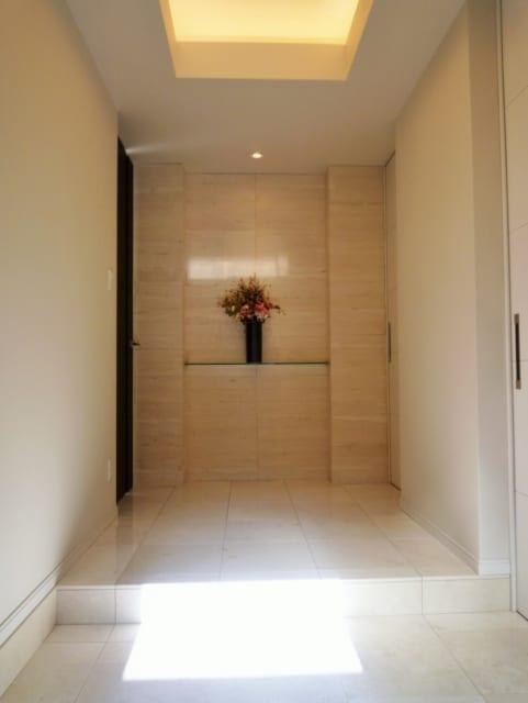 玄関ホール。大理石の床と飾り棚、天井の間接照明がラグジュアリー感を印象づける。