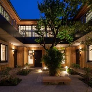 外観 中庭を北からのぞむ/建物は、中庭を囲むコの字型。黒格子の窓が連なる2階部分がオーナー邸。中庭や道路沿いにはシンボルツリーとなる大きなウメの木のほか、ハナミズキ、アジサイ、キンモクセイ、もみじ、ユズなどが豊かに植えられ、季節ごとに目を楽しませてくれる