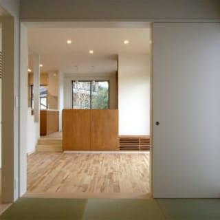 和室から見たリビング。奥にあるキッチン、ダイニングと段差を付けることで開放感を保ちながら区切られた空間となっている
