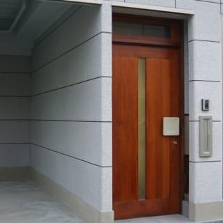外観、外玄関/ネイビーと砂利入りの白いタイル風塗装で仕上げた清潔感あふれる外観。3階建て建物の1階はKさんが営む建具業の工場と駐車場で、2階、3階が自宅。茶色の扉は外玄関。その先には自宅への内玄関に続くアプローチがある