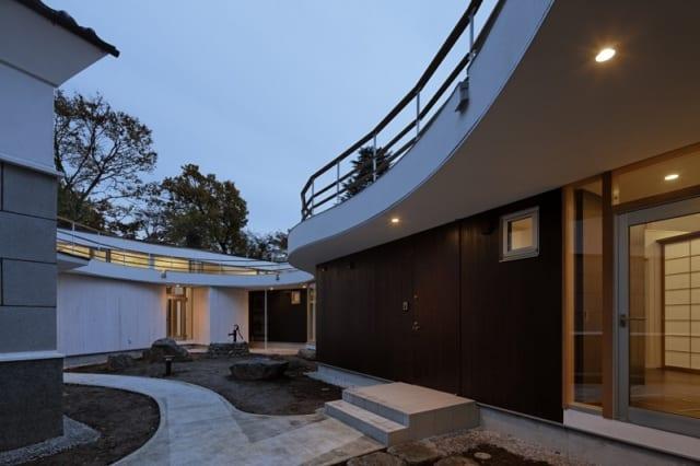 中庭/写真右が親世帯、写真左の蔵の先が子世帯。親世帯はダークブラン、子世帯は白を基調とし、世帯ごとに色味を変えて個性を出した。建物上部の手すりは両世帯をつなぐ屋上テラスのもの。テラスの美しい曲線に沿ってハイサイドの窓が連なり、空や木々の眺めとともにやわらかな光を邸内に届ける