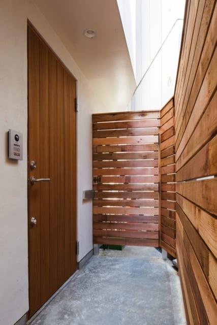 1階 自宅玄関 外観/建物横のアプローチを入るとまず店舗の出入口があり、その先に自宅の玄関扉がある。周囲はウッドフェンスで囲み、プライベート感を確保
