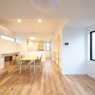 3階LDK リビング~ダイニング~キッチン/開放感あふれるLDK。写真右奥のキッチンの脇には冷蔵庫置場のほか、洗濯機置場もある。床材は濃淡のある木柄が温かな重厚感を漂わせるアカシア。