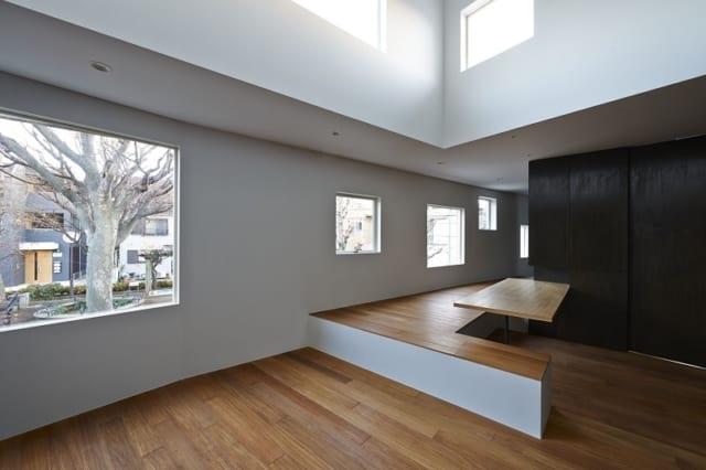 2階 リビング~ダイニング/一段高いスペースは、エントランス側の階段から上がった際にリビングへの通り道になる。しかし、単なる通路ではなく、くつろげる空間になるよう小上がりとし、堀座卓のダイニングテーブルも設置。床暖房入りで暖かく、反対側に椅子を置けば6名程度座れる。床は床暖房対応の素材の中から「リンゴア」を選択。高級感のある仕上がりに