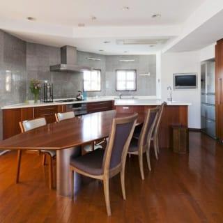 7階(自邸)ダイニング・キッチン/建物の高さ制限の関係で斜めにカットされた壁が空間に動きを生み、不思議な居心地のよさがある。合わせて造り付けのダイニングテーブルも斜めに設置し、テーブルまわりの空間を均等な広さに。おかげで動線がよく、デッドスペースもない