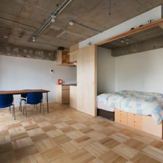 寝室/部屋の中央に据えられた寝室。ベッドの下は収納として利用することができる。開閉できる扉を開けると、リビングと一体化したスペースに