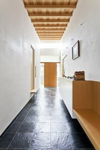 土間/親世帯の玄関から北の庭につながる、大きく長い土間。右の扉は親世帯への入り口。左の扉は子世帯のキッチンに近い勝手口。庭への出入口として子世帯一家も頻繁に使用する