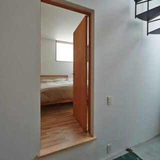 寝室/土間に対して高さを設けた寝室。壁の高い位置にもうけられた窓からは明るい光が差し込む