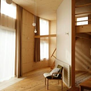 セカンドライフを想定して建てられたOさん邸は、コンパクトな平屋にロフトを備えたミニマムな空間。家具もできるだけ置かず、シンプルに暮らせるよう設計されている。壁や天井に張った合板は節が多く主張が強いため、LDの中央に立てた斜めの壁は白で塗装。カーテンもツヤのある無地のファブリックを採用し、全体の調和をはかった