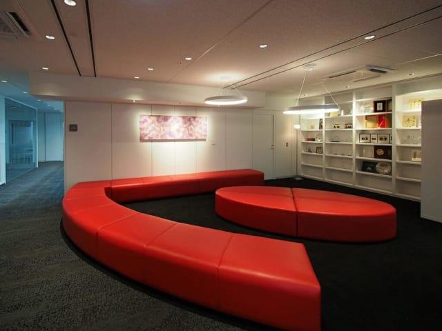 【テクマトリックス社】印象的な赤いソファが配置されたラウンジ。照明も含め、「楕円形」がモチーフになっている。