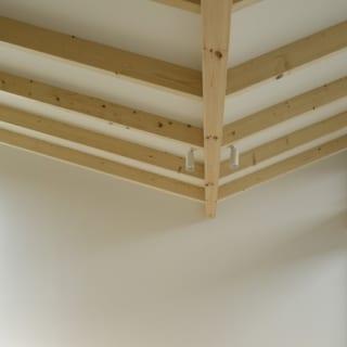 繁田諭   【写真3】C棟 2階 リビングダイニング/空間を邪魔しないシンプルな照明で、ユニークなV字の屋根が引き立っている。収納ベンチの背後には間接照明を設置し、室内をやさしい光で包む