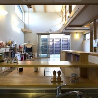 2階 キッチン/ダイニング、リビング、テラスを見渡せるキッチン。カウンター下の棚はダイニング側がスリガラスの引き戸付き(写真は外してある)で、食事中にちょっと調味料が欲しいときなどにサッと開けてとることができる。写真右手は水まわりに続き、家事動線もよい