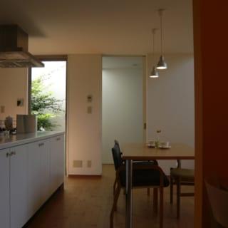 アイランドキッチンの前面には、食器などを大量収納できて見た目もすっきり。横の開口部からは坪庭の緑が見える
