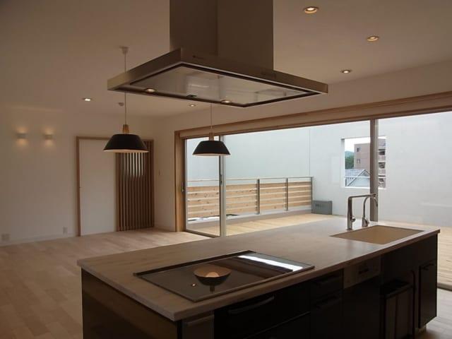 キッチンから望むリビングとデッキテラス。視界の抜けと広がり感がある。