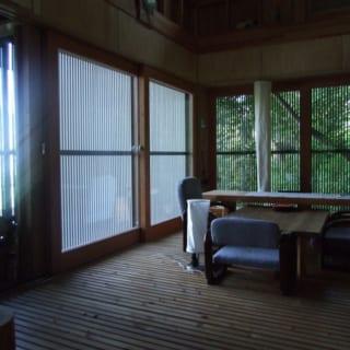 1階のスノコ床の居間の一角。窓一面に見える木々に囲まれ、山のなかにいることが実感できる