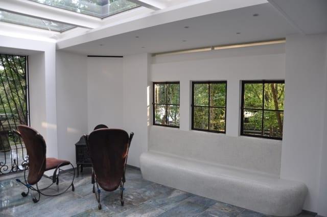 テラスハウス内部 西側/アンティークの窓枠を使用した3連窓の下には、座り心地のよいベンチを設置。天井と壁の合間につくったガラス張りの細長い隙間は、空間を軽やかに感じさせる効果がある。日が落ちるころ、西の隙間からスッと差し込む外光も美しい