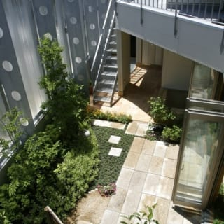 外観/角地に立つK邸は、通りに面した庭側が半透明の高い塀で囲われている。光は通すが中の様子はわからず、しっかりとプライバシーを守ることができる