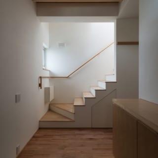 玄関ホール/真っ白な漆喰の壁と優しい木目が特徴のカバザクラの床、構造材を見せるスタイルをとった天井など、限りなくシンプルでありながらこだわりの感じられるホール。外階段同様、階段下は生活用品などを入れておける物入れになっている
